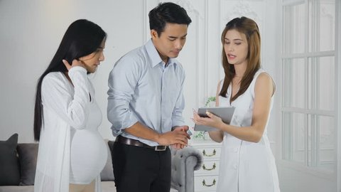 The young man holding a pregnant wife to see the furniture in the showroom. Young sales employee make the catalogue with the tablet and recommended customers sit down on the beautiful couch