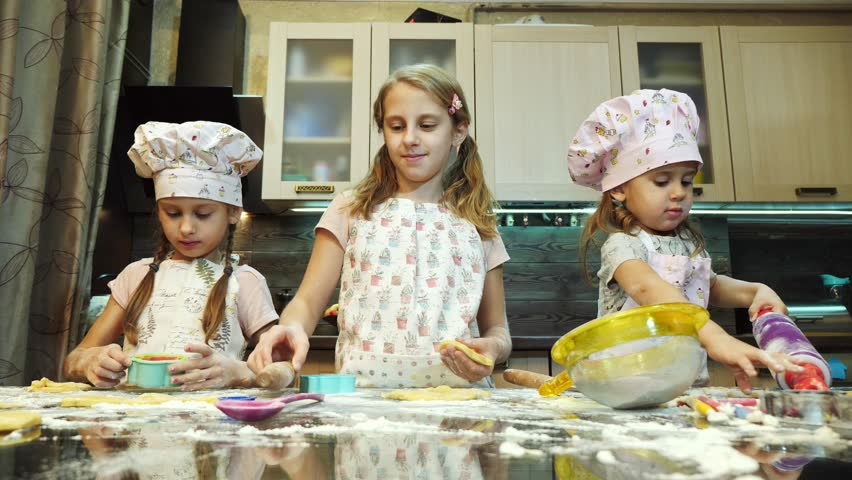 A small girls rolling dough and cutting out cookies of dough   Shutterstock HD Video #1007987089