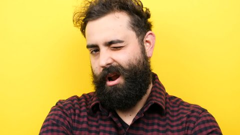 Attractive bearded man winks silly on yellow background in slow motion