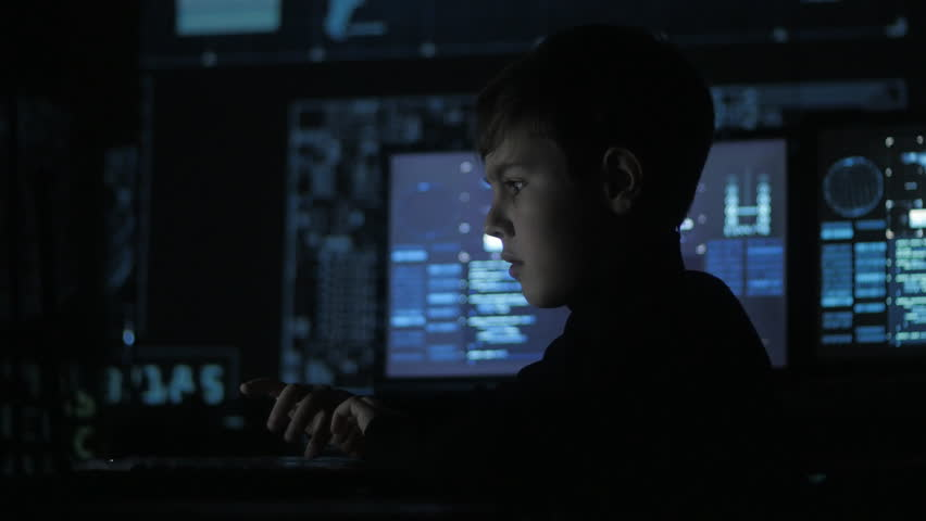 Cute teen boy programmer working at a computer in the data center filled with display screens. Portrait of Child prodigy hacker.