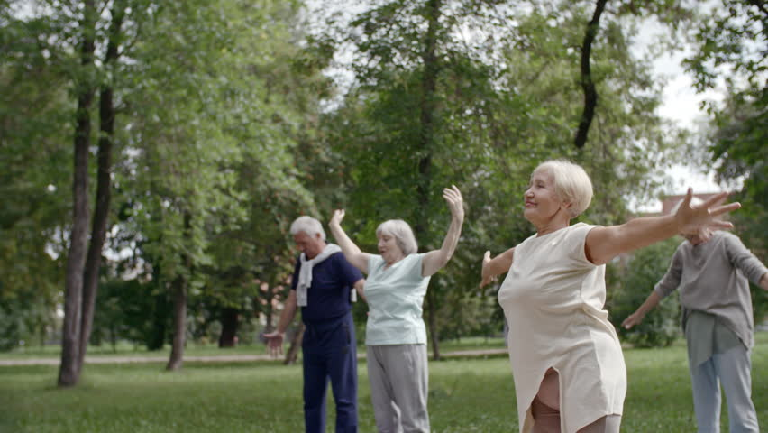 Tracking shot of group of elderly people doing warming up exercises, stretching and breathing deeply in and out in park