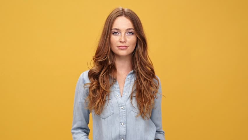 Smiling ginger woman in denim shirt puts on her hat and posing with crossed arms while looking at camera over yellow background