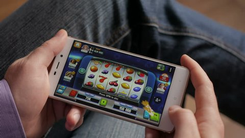 Casino slot machine app on mobile screen against  hand of man using smartphone. Gambling addicted man in front of online casino slot-machine on mobile phone. 4K UHD.  LOS ANGELES - February 2018.