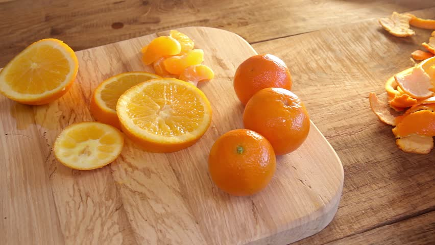 cutted oranges and tangerines on wooden background