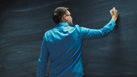 Young Man Writing without Writing on the Blackboard. Great for the Template. Shot on RED EPIC-W 8K Helium Cinema Camera.