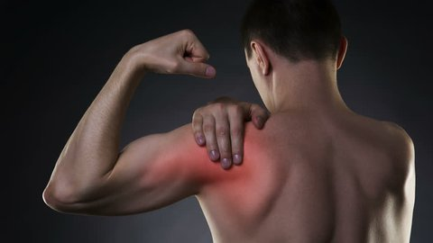 Cinemagraph:  Man with pain in shoulder on black background, studio shot with red dot