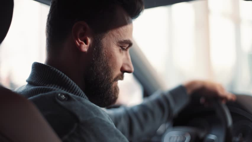 Handsome young man with beard sitting at wheel of car, talking. Guy choosing car, touching chair, wheel, viewing interior of automobile .   Shutterstock HD Video #1008067609