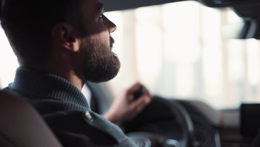 Handsome young man sitting at wheel of car, saying something. Guy spending time in traffic jam and looking at car's interior. Close-up.   Shutterstock HD Video #1008068089