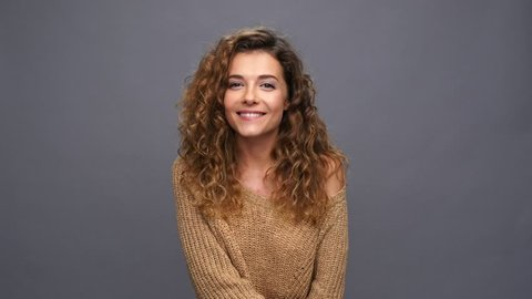 Smiling curly woman in sweater showing silence gesture over purple background