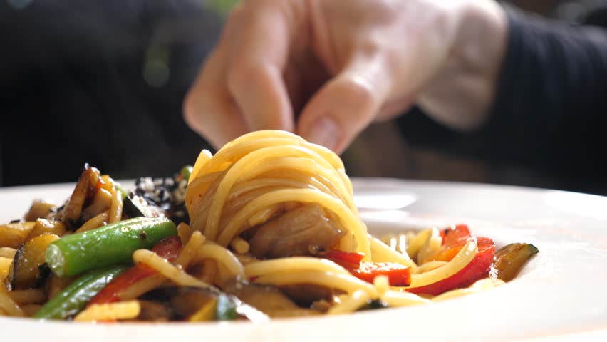 Italian cuisine in restaurant woman eating spaghetti pasta with vegetables with a fork closeup