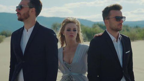 Blonde is standing between two boyfriends in a desert. Strange relationships of woman with two man, abstract shot on a beach