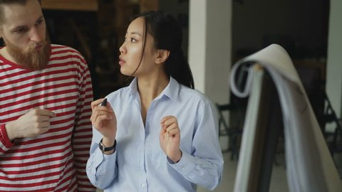 Cheerful asian girl explaining start-up project on flipchart to hipster male colleague at loft office