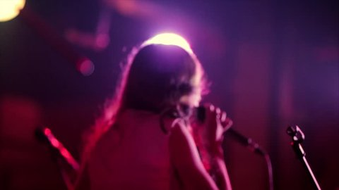 Back view of girl singer in stage lights