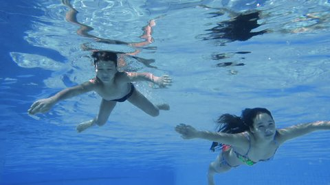 Boy and girl dive in swimming pool together, underwater slow motion