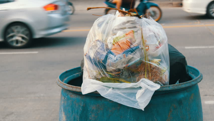 A full garbage can with large garbage bags full of leftover food and waste is on the street passing cars, motorcycles and bicycles