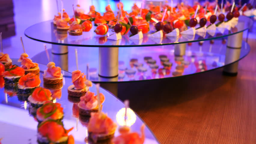 Beautifully decorated catering banquet table with different food snacks and appetizers on corporate christmas birthday party event or wedding celebration.