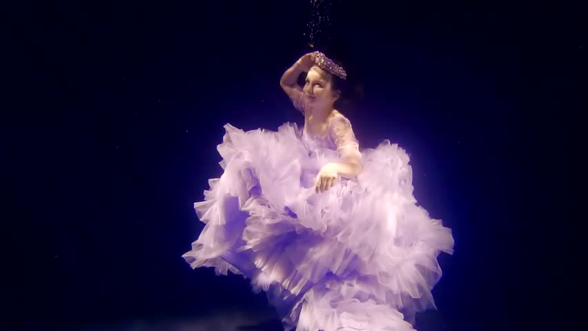 calm and smiling little actress is diving under water in large aquarium, her long dress is floating around