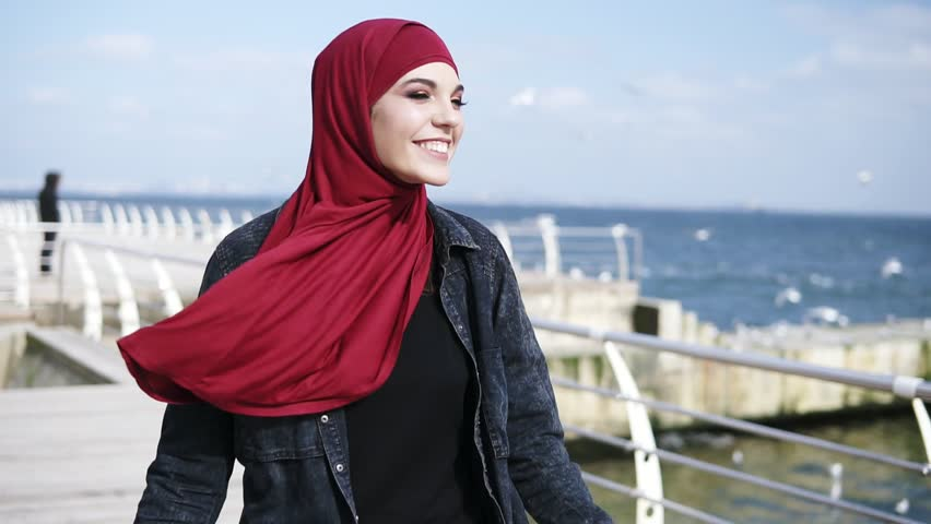 Attractive muslim girl with hijab is smiling and going back and forth, enjoying her sea side walk. Free time activities. Outdoors footage