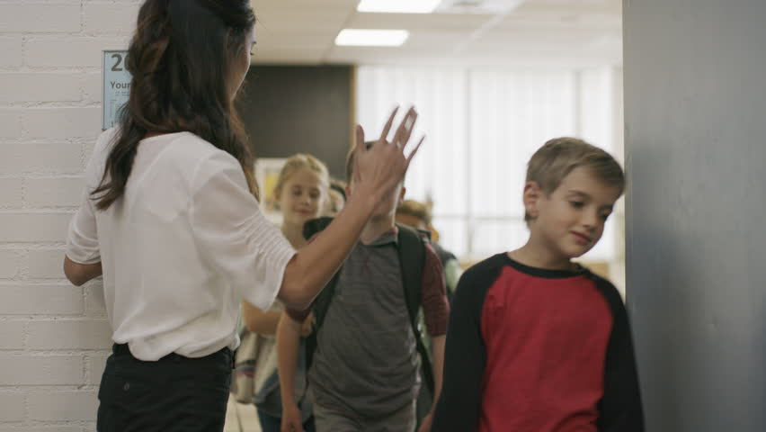 Enthusiastic teacher high-fiving students exiting doorway from classroom / Provo, Utah, United States