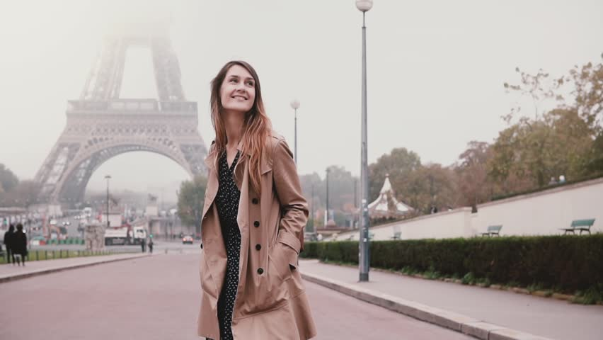 Young attractive woman walking near Eiffel tower in Paris, France. Happy girl looking around and smiling. Slow motion. | Shutterstock HD Video #1008239179