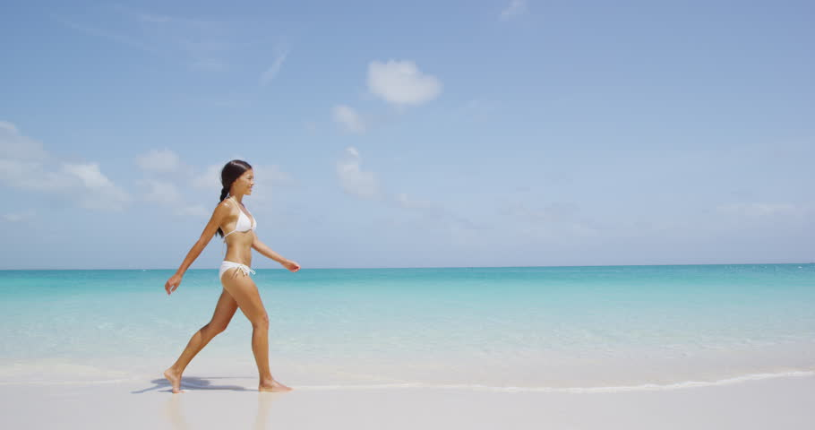 Beach vacation travel woman relaxing in bikini walking on perfect tropical paradise Caribbean beach with turquoise ocean water during summer vacations holidays. Happy lifestyle Asian girl. SLOW MOTION