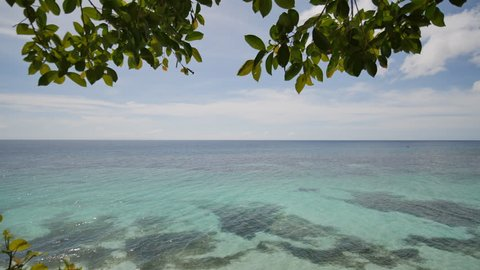 View from the height of the balcony to the ocean and coral reefs of the shallow waters of the Philippine tropics. Exotic green beach.