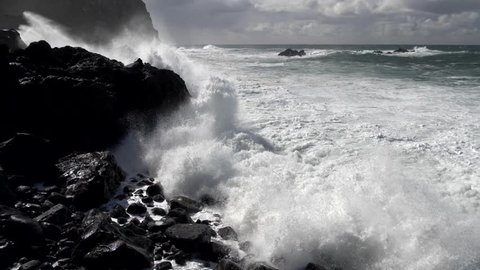 Spray from crashing waves drifting over high rocky outcrops. Slow motion shot.