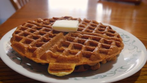 Pouring maple syrup onto a golden brown waffle at brunch in 4k. A pat of butter melts into the stack of waffles. Vermont maple syrup pours from a ceramic crock. The breakfast food is a family favorite