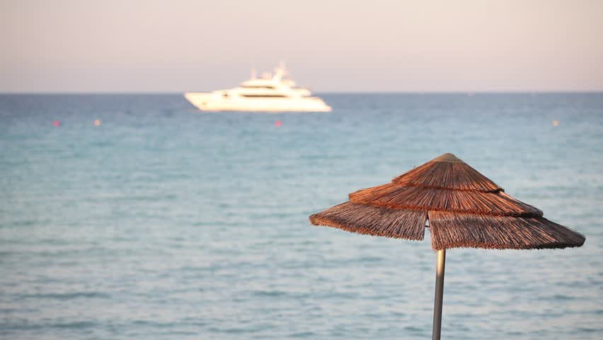 Sun straw umbrella on the background of the sea and white motor yacht, sand beach with sun umbrellas at sunset, Yacht Vacation Vast Seascape, white motor yacht at sea at sunset, sea resort in Cyprus