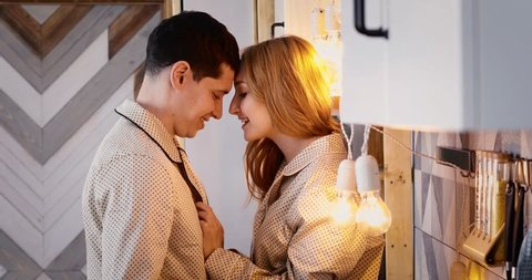 Young beautiful couple in kitchen. Family of two preparing food. Woman sitting on kitchen tabletop and kissing her man to. Nice loft interior with light bulbs