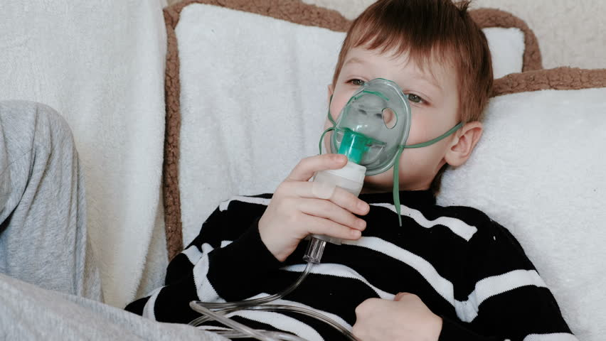 Using nebulizer and inhaler for the treatment. Boy inhaling through inhaler mask lying on the couch.
