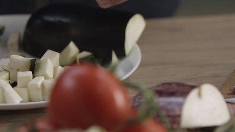 Cutting aubergine. Cooking homemade ratatouille. Healthy eating concept. Slow motion