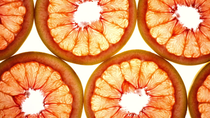 Amazing top view of grape-fruit slices in flat lay close up, rotating contra clockwise. Excellent food macro background with vibrant texture and backlight in UHD 4k, 3840x2160, clip.