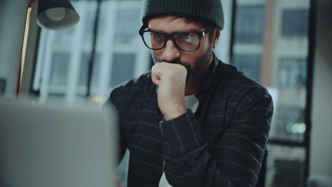 Bearded hipster man wearing eye glasses and using devices at office. Confident busy male freelancer in trendy eyewear using laptop while surfing net searching information for presentation
