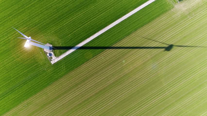 Aerial top down view wind turbine in polder landscape showing shadow from sun and sun reflection on top of construction wind turbine is device that converts winds kinetic energy into electrical energy