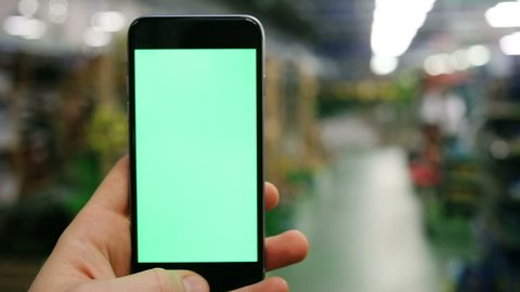 man hand using smart phone with green screen in the plant market / close-up chroma key mock up hypermarket tapping pointing finger display app store business swapping tap internet surfing market