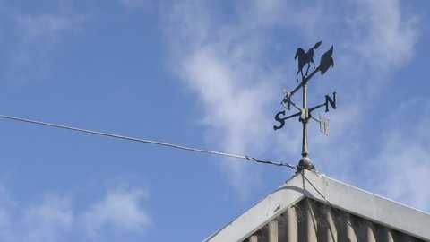 A steady zoomed in shot of a wind vane from a stable's roof.