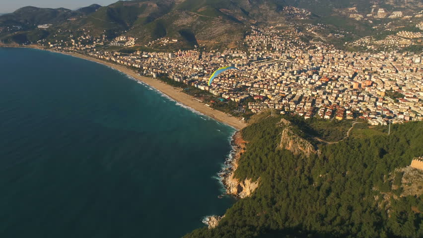 Aerial drone view of parashute jumper flying over beautiful Alanya, Mediterranean sea, famous Fortress on rocky hills of Taurus mountains in Antalya Province, Turkey. | Shutterstock HD Video #1008317419