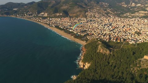 Aerial drone view of parashute jumper flying over beautiful Alanya, Mediterranean sea, famous Fortress on rocky hills of Taurus mountains in Antalya Province, Turkey.