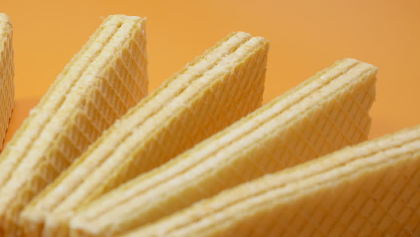 Wafers manufactured by an industrial method lie on an orange background. Sweets are crispy. Smooth rotation