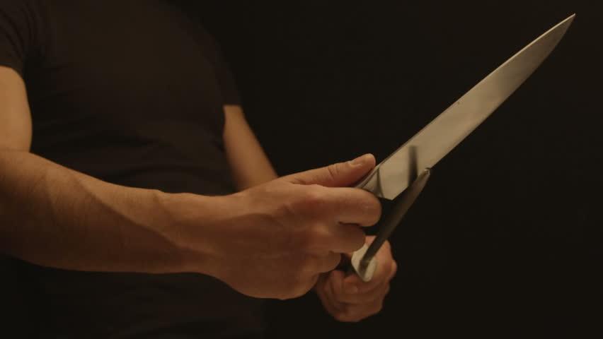 Man sharpens a knife on a sharpener