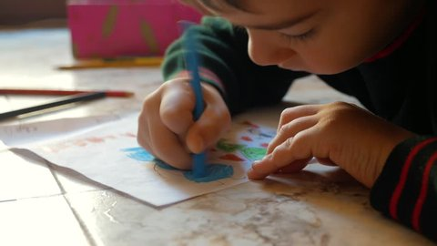 The child draws on paper