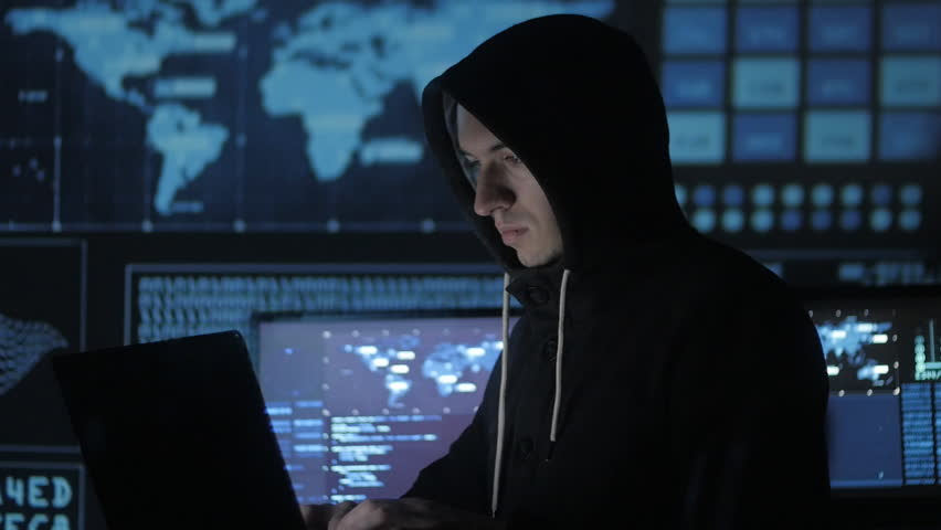 Man geek hacker in hood working at computer in cyber security center filled with display screens. | Shutterstock HD Video #1008364879