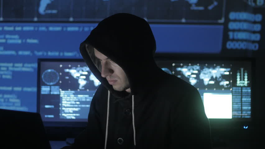 Man geek hacker in hood working at computer while blue code characters reflect on his face in cyber security center filled with display screens. | Shutterstock HD Video #1008364909