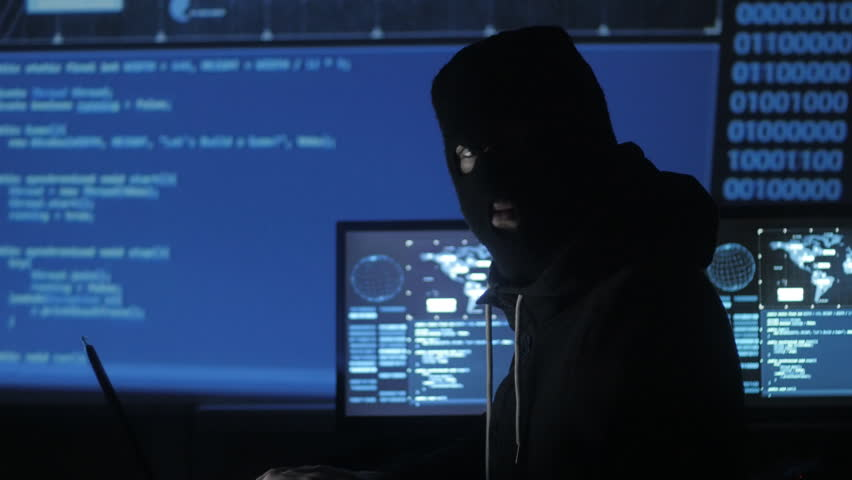 Dangerous hacker in the mask tries to enter the system using codes and numbers to find out the security password. The concept of cybercrime. | Shutterstock HD Video #1008364969
