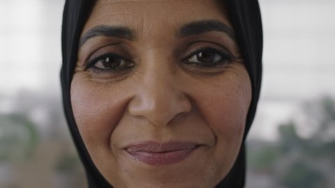 close up portrait of middle aged muslim business woman smiling looking cheerful at camera wearing traditional headscarf mature experienced female in office workspace slow motion