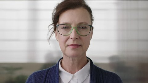 portrait of successful senior business woman boss looking serious confident at camera wearing glasses in office workspace background close up
