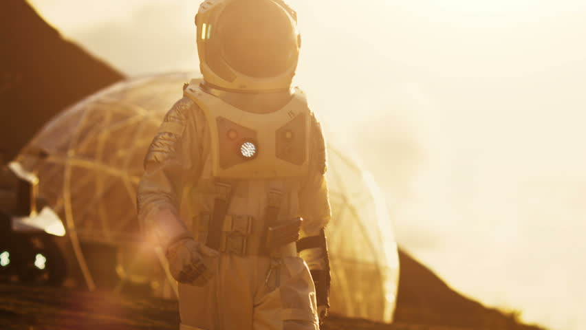 Astronaut Wearing Space Suit Walks on the Red Planet/ Mars. In the Background His Base with Rover Parked, Hot Red Daylight Sun Shines. Shot on RED EPIC-W 8K Helium Cinema Camera.