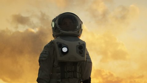 Low Angle Shot of Female Astronaut in the Space Suit Looking Around Alien Planet. Advanced Technologies, Space Travel, Colonization Concept. Shot on RED EPIC-W 8K Helium Cinema Camera.