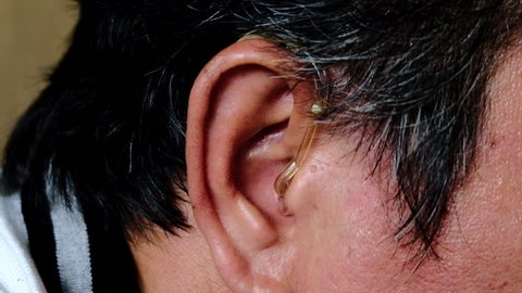Asian man wearing a hearing aid on his right ear.